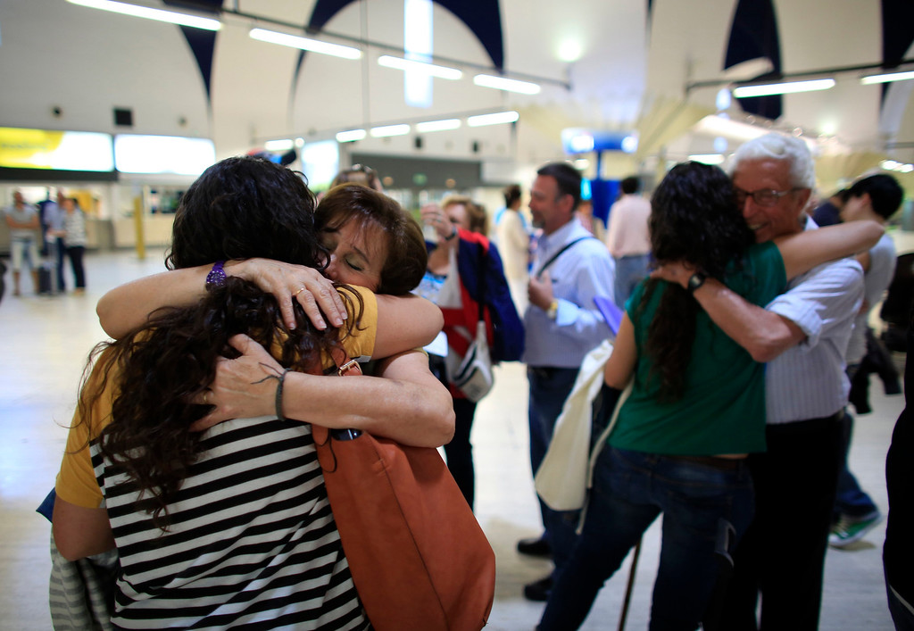 . Spanish nurses Maria Teresa Marin (L), 23, embraces her mother Nati, 65, as her twin sister Maria Jose (2nd R), embraces her father Jose Manuel, 79, before boarding a plane to Amsterdam at San Pablo airport in Seville, southern Spain, June 4, 2013. After months of studying Dutch, a group of young Spanish nurses moved to the Netherlands to take up work, fleeing a dismal job market at home. Spain\'s population dropped last year for the first time on record as young professionals and immigrants who moved here during a construction boom head for greener pastures. Spain\'s jobless rate is 27 percent, and more than half of young workers are unemployed. For Spanish nurses, the Netherlands\' nursing deficit is a boon. Picture taken June 4, 2013.  REUTERS/Marcelo del Pozo