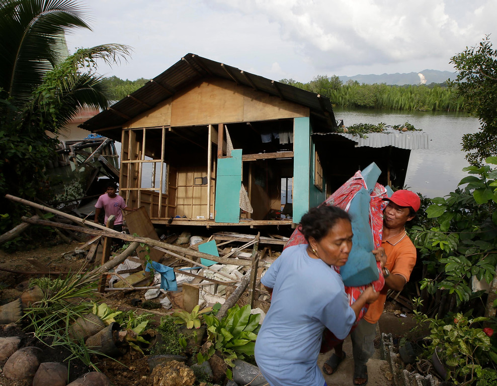 . A couple save their belongings from their half-submerged home which was damaged by Tuesday\'s 7.2-magnitude earthquake in Cortes township, Bohol province in central Philippines Wednesday, Oct. 16, 2013.  (AP Photo/Bullit Marquez)