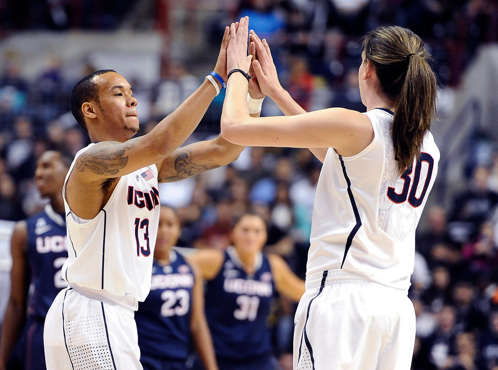 . Connecticut\'s Shabazz Napier, left, high-fives teammate Breanna Stewart during an inter-squad scrimmage at the men\'s and women\'s basketball teams\' First Night event in Friday, Oct. 18, 2013, in Storrs, Conn. (AP Photo/Jessica Hill)