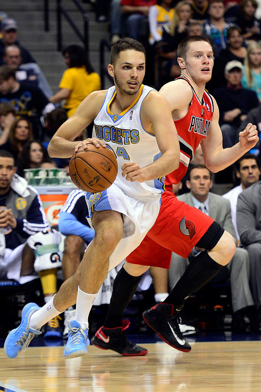 . DENVER, CO - APRIL 14: Evan Fournier (94) of the Denver Nuggets drives around Luke Babbitt (8) of the Portland Trail Blazers during the first half of action. The Denver Nuggets play the Portland Trail Blazers at the Pepsi Center. (Photo by AAron Ontiveroz/The Denver Post)