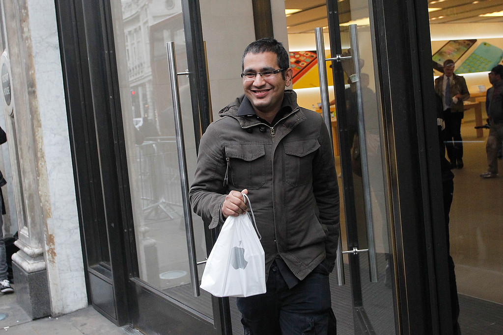 . An excited customer leaves the Apple store this morning with his new iPhone5S, on Regent Street on September 20, 2013 in London, England.  (Photo by Mary Turner/Getty Images)