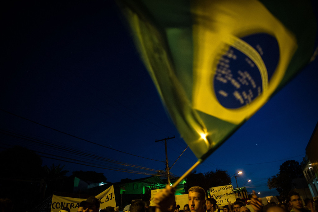 . A Brazilian flag is waved during a demonstration in Belo Horizonte, Brazil, on June 21, 2013.  AFP PHOTO / YASUYOSHI  CHIBA/AFP/Getty Images