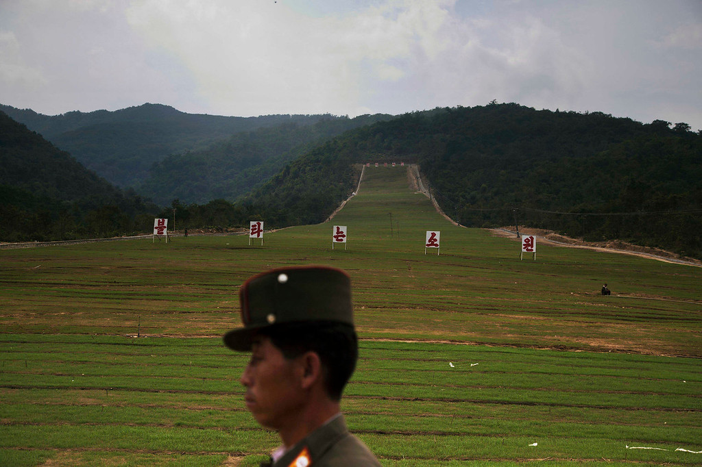 """. A North Korean soldier passes by a ski slope under construction at North Korea\'s Masik Pass on Friday Sept. 20, 2013. The signs on the slope together read, \""""Burning Hope.\"""" North Korean authorities have been encouraging a broader interest in sports in the country, calling it \""""the hot wind of sports blowing through Korea.\"""" (AP Photo/David Guttenfelder)"""