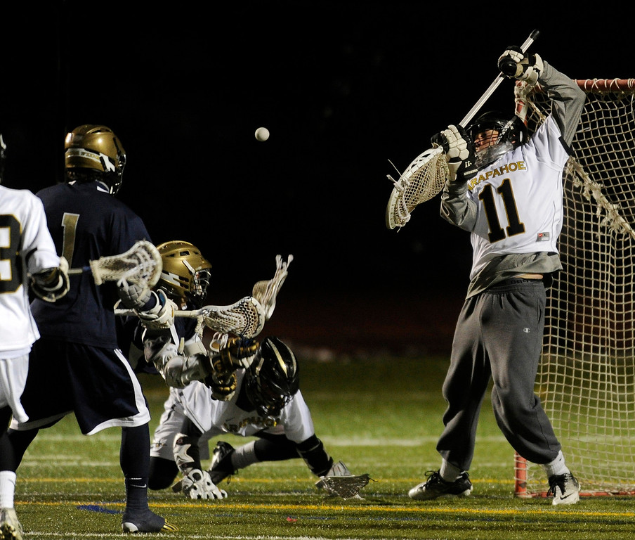 . LITTLETON, CO. - APRIL 10: Warriors goalie Ryan Smith (11) made a save in the fourth quarter. The Mullen High School boy\'s lacrosse team defeated Arapahoe 8-7 Wednesday night, April 10, 2013. Photo By Karl Gehring/The Denver Post)