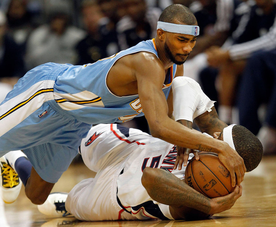 . Denver Nuggets small forward Corey Brewer, top, and Atlanta Hawks small forward Josh Smith (5) scramble for a loose ball during the second half of an NBA basketball game on Wednesday, Dec. 5, 2012, in Atlanta. (AP Photo/John Bazemore)