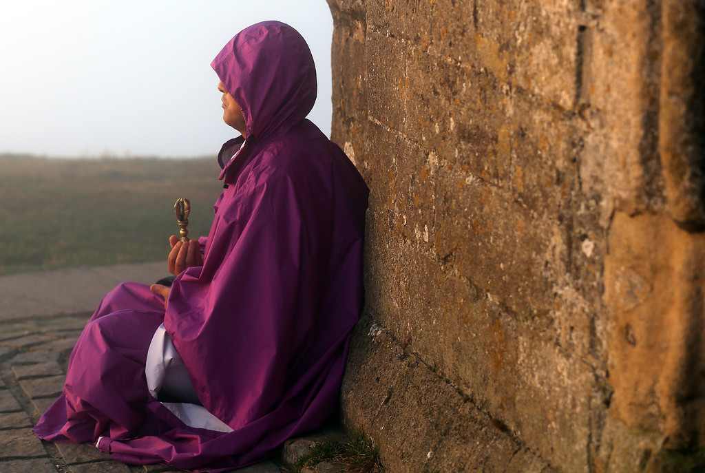 . A visitor to Glastonbury Tor meditates beside St. Michael\'s Tower, a ruined 14th-century church tower, as the sun rises and begins to clear the early morning mist and fog near the town of Glastonbury on September 4, 2013 in Somerset, England.   (Photo by Matt Cardy/Getty Images)