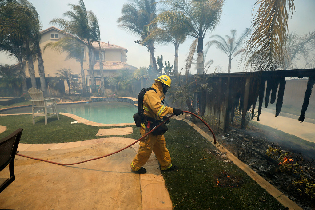 . A Firefighter puts water on a house fence during a wildfire Wednesday, May 14, 2014, in Carlsbad, Calif. More wildfires broke out Wednesday in San Diego County threatening homes in Carlsbad and forcing the evacuations of military housing and an elementary school at Camp Pendleton as Southern California is in the grip of a heat wave. (AP Photo)