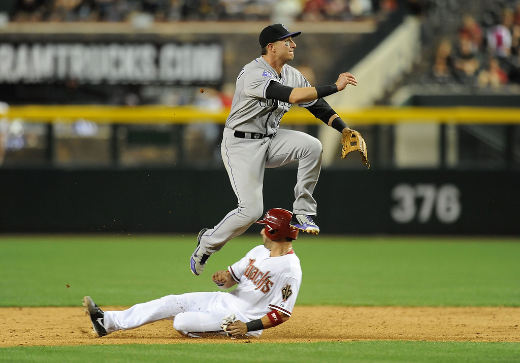 . PHOENIX, AZ - APRIL 25:  Troy Tulowitzki #2 of the Colorado Rockies turns a double play as Wil Nieves #27 of the Colorado Rockies slides into second base at Chase Field on April 25, 2013 in Phoenix, Arizona.  (Photo by Norm Hall/Getty Images)