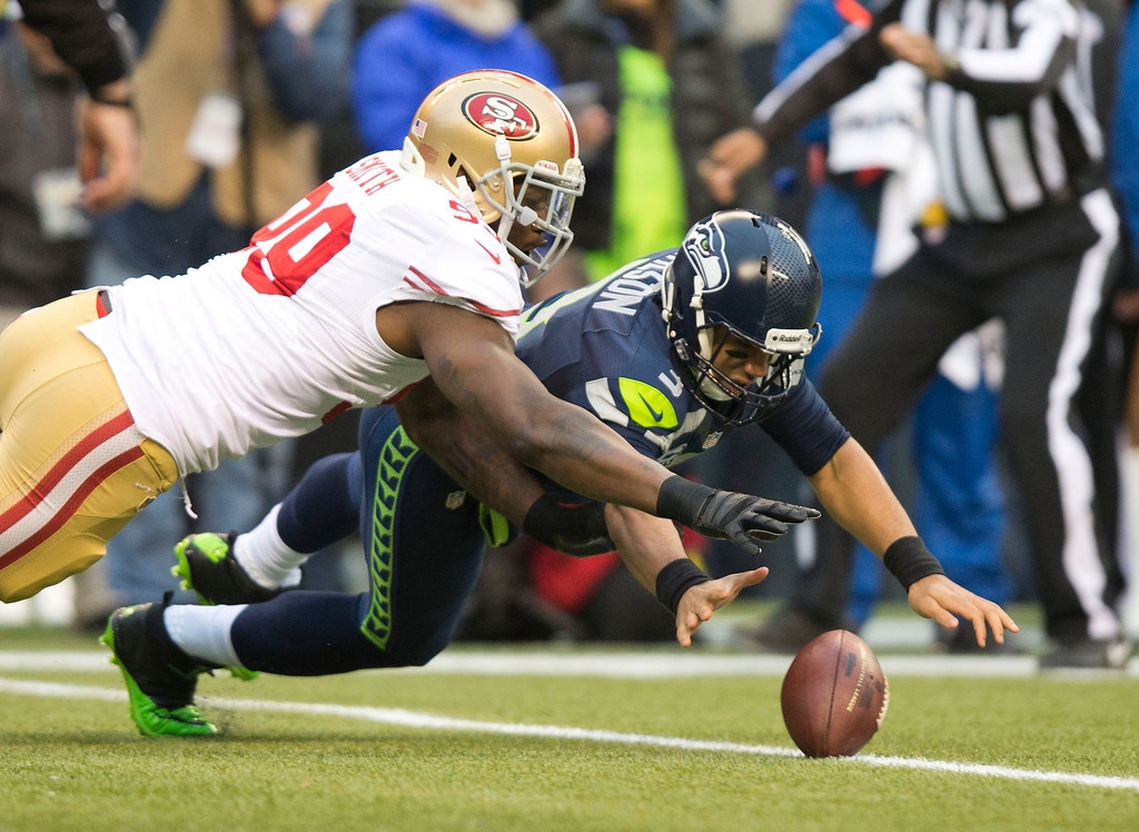 . San Francisco 49ers outside linebacker Aldon Smith (99) goes after the ball on the first play of the game by Seattle Seahawks quarterback Russell Wilson (3) during the NFL football NFC Championship game Sunday, Jan. 19, 2014, in Seattle. Smith recovered the ball. (AP Photo/The Sacramento Bee, Hector Amezcua)