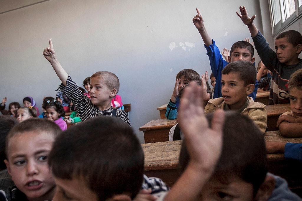 . In this Thursday, Sept. 26, 2013 photo, Syrian children attend class at the public school in Madaya village as classes begin in the Idlib province countryside of Syria. Millions of Syrian children most of them in government-controlled areas have returned to school in the past two weeks, despite the conflict that according to UNICEF has left 4,000 Syrian schools or one in five damaged, destroyed or sheltering displaced families. (AP Photo)