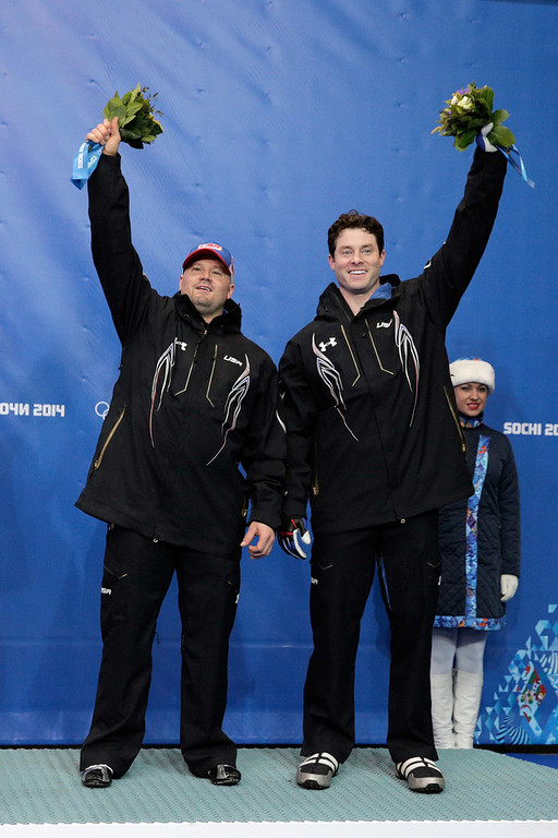 . Bronze medalists Steven Holcomb and Steven Langton of the United States team 1 celebrate during the flower ceremony for the Men\'s Two-Man Bobsleigh on Day 10 of the Sochi 2014 Winter Olympics at Sliding Center Sanki on February 17, 2014 in Sochi, Russia.  (Photo by Adam Pretty/Getty Images)