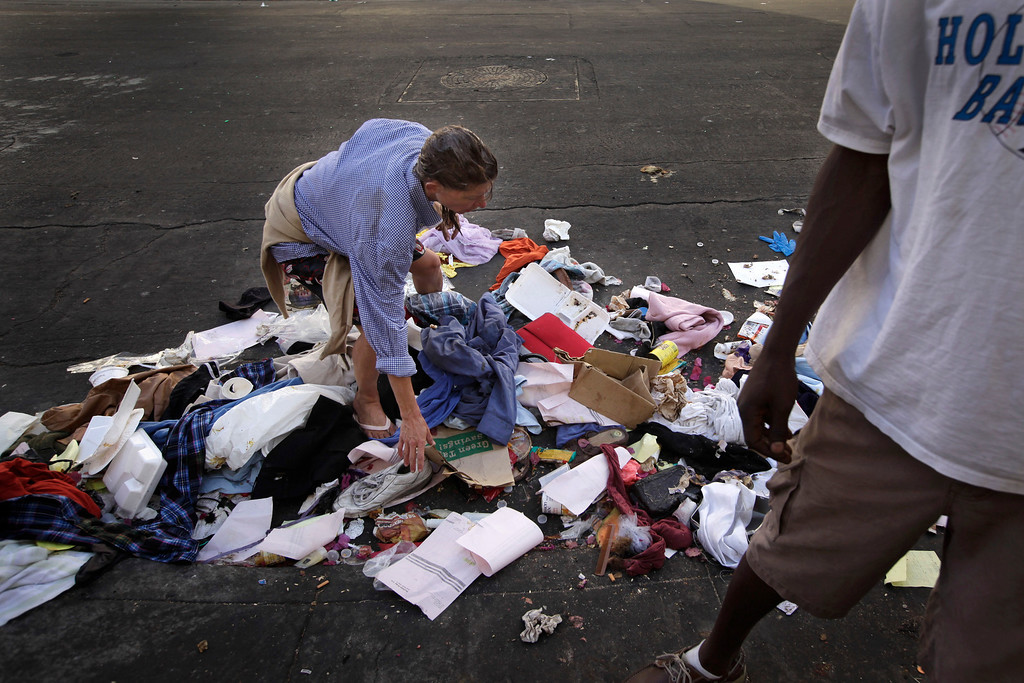 . A homeless woman looks through a pile of trash for anything useful in the Skid Row area of Los Angeles, Wednesday, July 3, 2013. (AP Photo/Jae C. Hong)