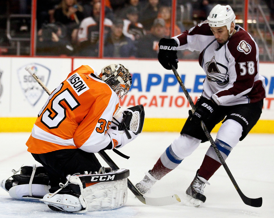 . Philadelphia Flyers\' Steve Mason, left, gloves the puck as Colorado Avalanche\'  Patrick Bordeleau, right, moves in during the first period of an NHL hockey game, Thursday, Feb. 6, 2014, in Philadelphia. (AP Photo/Tom Mihalek)