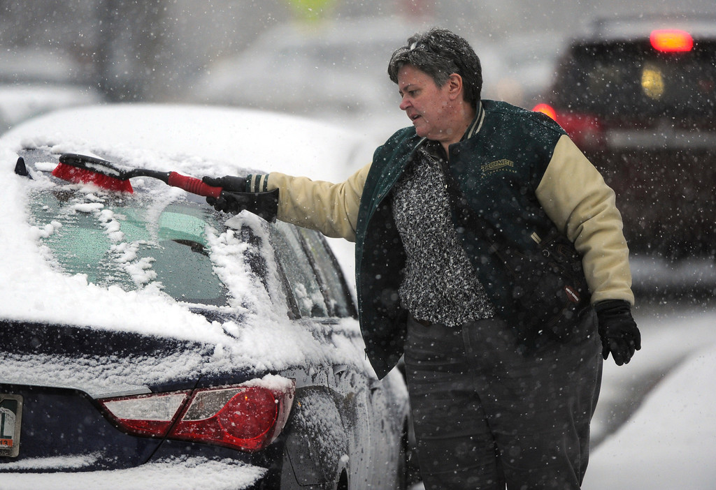 . DENVER, CO. - FEBRUARY 20:  University of Denver administrator Joanna Patrick cleared snow from her car after work Wednesday evening, February 20, 2013. The Denver metro area is expecting 4-6 inches of snow overnight. (Photo By Karl Gehring/The Denver Post)