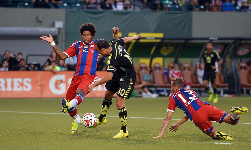 . Landon Donovan of MLS All-Stars scores his teams second goal against Dante and Rafinha of Muenchen during the MLS All-Star game between the MLS All-Stars and FC Bayern Muenchen at Providence Park on August 6, 2014 in Portland, Oregon.  (Photo by Lars Baron/Bongarts/Getty Images)