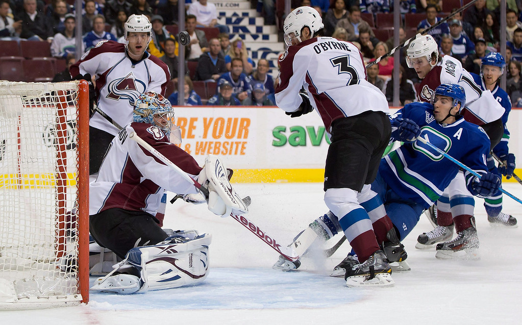 . Colorado Avalanche goalie Semyon Varlamov, left, of Russia, stops Vancouver Canucks\' Alex Burrows, right, as, from left to right, Colorado\'s Jan Hejda, of the Czech Republic, Ryan O\'Byrne and Jamie McGinn defend during the first period of an NHL hockey game in Vancouver, British Columbia, Thursday, March 28, 2013. (AP Photo/The Canadian Press, Darryl Dyck)