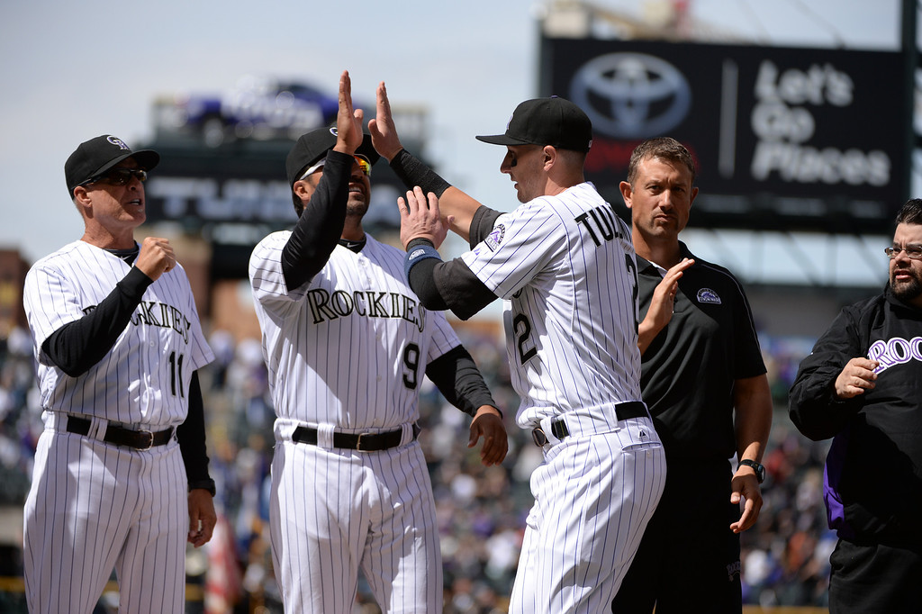 . Troy Tulowitzki (2) high fives Special Assistant Vinny Castilla (9) as the starting lineup is announced before the game. (Photo by Hyoung Chang/The Denver Post)