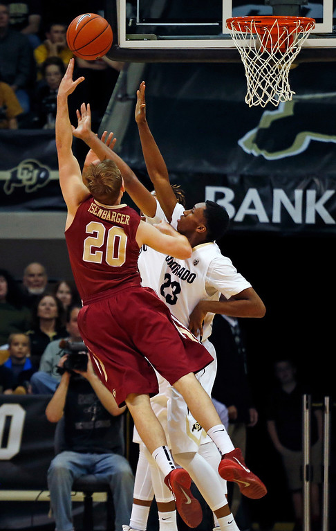 . Elon\'s Jack Isenbarger, left, shoots covered by Colorado\'s Jaron Hopkins during an NCAA college basketball game in Boulder, Colo., Friday, Dec. 13, 2013. (AP Photo/Brennan Linsley)