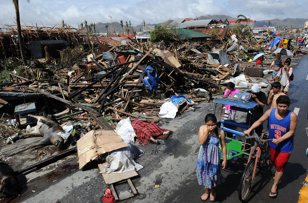 . Residents walk past bodies and destroyed houses along a road in Tacloban, on the eastern island of Leyte on November 10, 2013 after Super Typhoon Haiyan swept over the Philippines.    TED ALJIBE/AFP/Getty Images