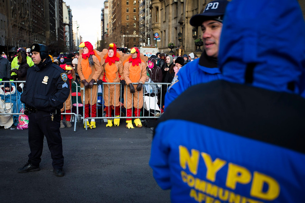 . Spectators dressed as turkey stand behind police barricades as they wait for the 87th Annual Macy\'s Thanksgiving Day Parade, Thursday, Nov. 28, 2013, in New York. After fears the balloons could be grounded if sustained winds exceeded 23 mph, Snoopy, Spider-Man and the rest of the iconic balloons received the all-clear from the New York Police Department to fly between Manhattan skyscrapers on Thursday.  (AP Photo/John Minchillo)