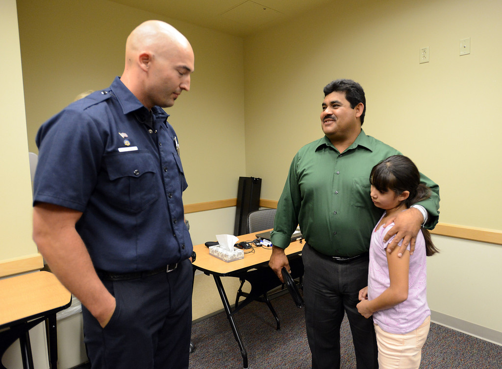 . North Metro Fire Rescue engineer John Cook, left, talks to  Roy Ortiz with his daughter Evelyn, 11, after a news conference at Good Samaritan Hospital on Friday.  Cook performed a swift water rescue to save Ortiz after plunging onto the water the water at Dillon Road last Thursday.  September 13, 2013 staff photo/ David R. Jennings
