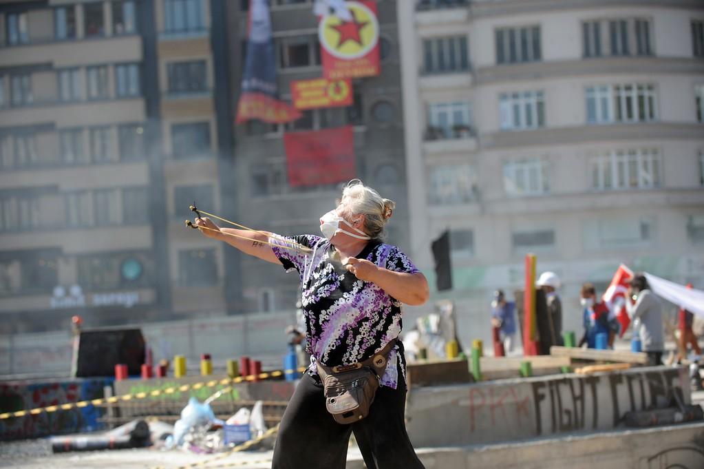 . A protestors uses a slingshot against Turkish riot police on Taksim square on June 11, 2013. AFP PHOTO / BULENT  KILIC/AFP/Getty Images