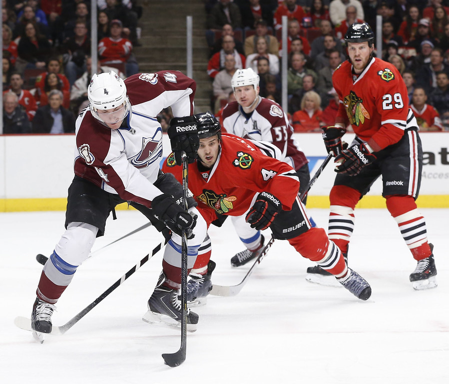 . Colorado Avalanche defenseman Tyson Barrie (4) handles the puck in front of the Chicago Blackhawks\'s goal as defenseman Niklas Hjalmarsson (4) and Bryan Bickell (29) defend during the first period of an NHL hockey game Tuesday, March 4, 2014, in Chicago. Also watching the play is Coilorado\'s Cody McLeod (55).  (AP Photo/Charles Rex Arbogast)