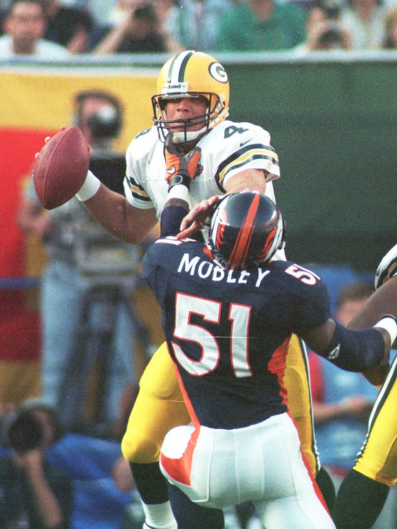 . Caption: Green Bay Packers Brett Favre is chased by John Mobley  during the first half of the Super Bowl XXXII in San Diego CA. (John Leyba/The Denver Post)