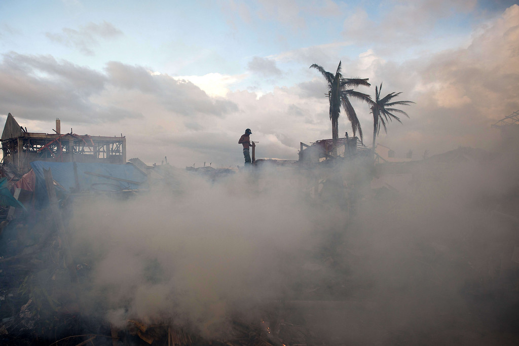 . A typhoon survivor builds a temporary shack as smoke rise from burning trash and debris in Palo on November 21, 2013.  AFP PHOTO/ Nicolas ASFOURI/AFP/Getty Images