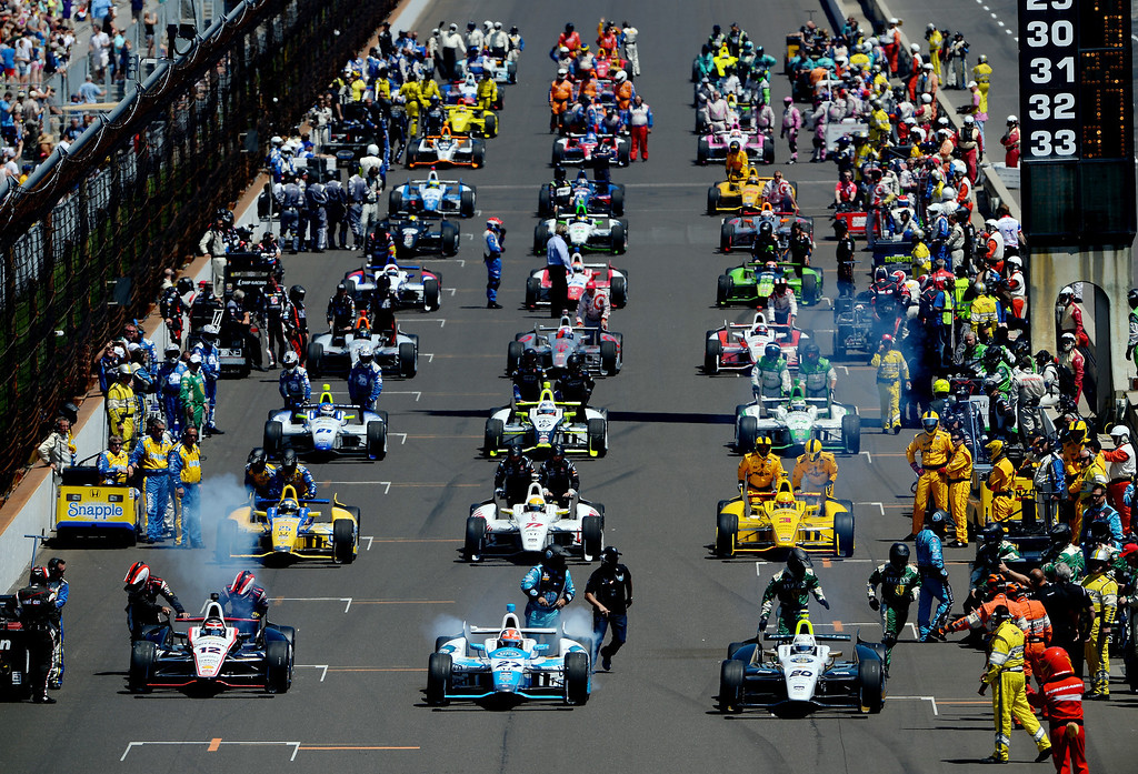 . Will Power of Australia, driver of the #12 Verizon Team Penske Chevrolet Dallara, James Hinchcliffe, driver of the #27 Andretti Autosport Honda Dallara, and Ed Carpenter, driver of the #20 Fuzzy\'s Vodka / Ed Carpenter Racing Chevrolet Dallara, lead the start the 98th running of the Indianapolis 500 at Indianapolis Motorspeedway on May 25, 2014 in Indianapolis, Indiana.  (Photo by Robert Laberge/Getty Images)