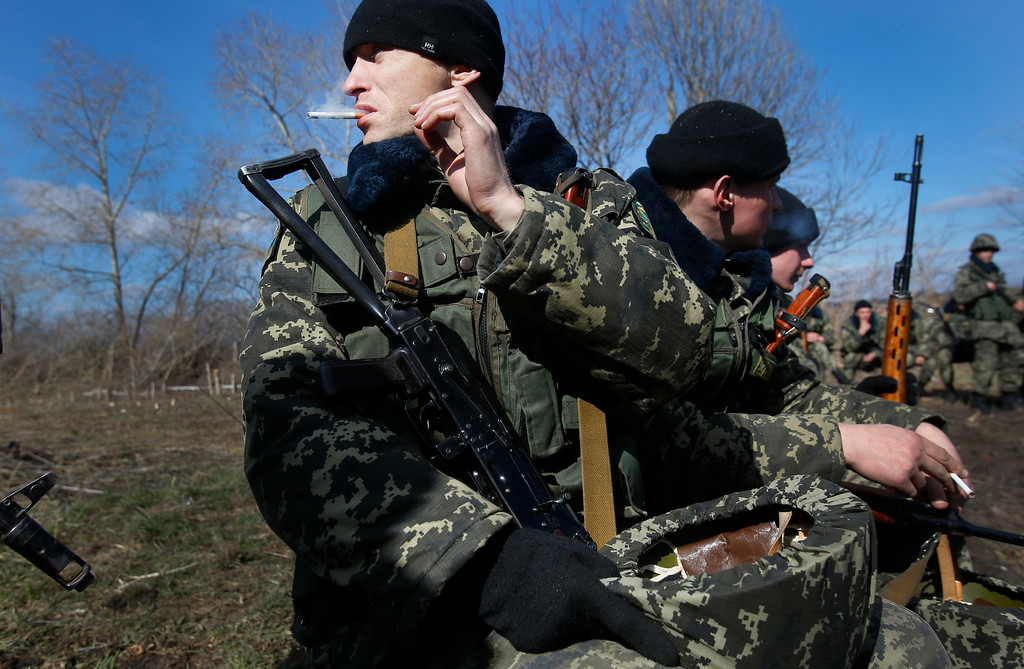 . Ukrainian border guards take a break during training at a military camp in the village of Alekseyevka on the Ukrainian-Russian border, eastern Ukraine, Friday, March 21, 2014. (AP Photo/Sergei Grits)