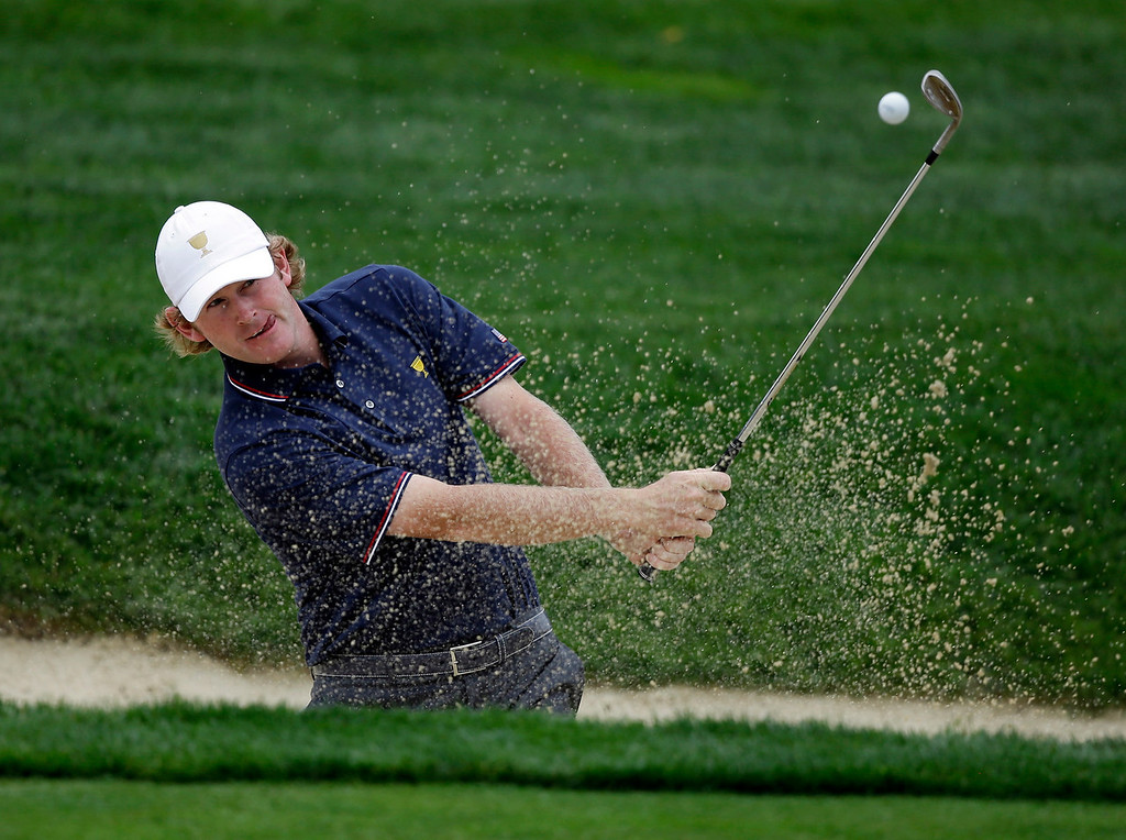 . United States team player Brandt Snedeker hits out of a bunker on the first hole during the four-ball match at the Presidents Cup golf tournament at Muirfield Village Golf Club Thursday, Oct. 3, 2013, in Dublin, Ohio. (AP Photo/Darron Cummings)