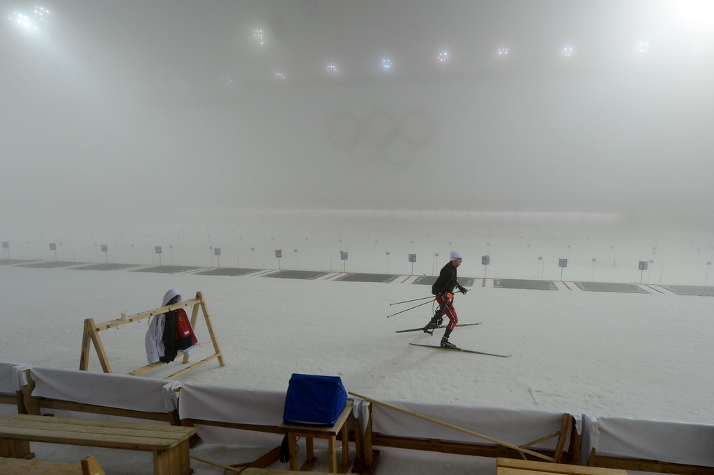 . A skier pass by the shooting range as the Men\'s Biathlon 15 km Mass Start has been postponed until the next day due to fog at the Laura Cross-Country Ski and Biathlon Center during the Sochi Winter Olympics on February 16, 2014, in Rosa Khutor, near Sochi.  KIRILL KUDRYAVTSEV/AFP/Getty Images
