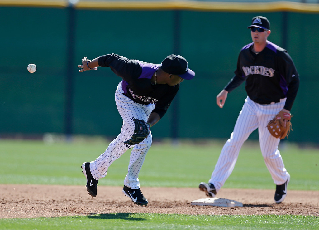. Colorado Rockies\' Jonathan Herrera, left, tosses the baseball to teammate Lars Davis during a spring training baseball workout on Sunday, Feb. 17, 2013, in Scottsdale, Ariz. (AP Photo/Darron Cummings)