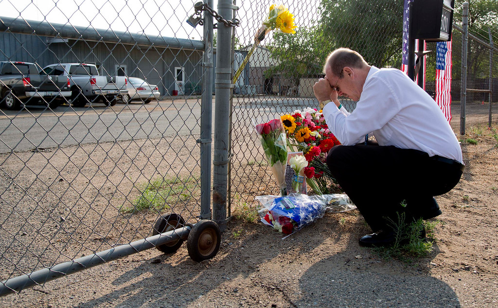 . Bob Hoskovec says a prayer as he kneels outside the gate of the Granite Mountain Interagency Hot Shot Crew fire station, Monday, July 1, 2013, in Prescott, Ariz.   (AP Photo/Julie Jacobson)