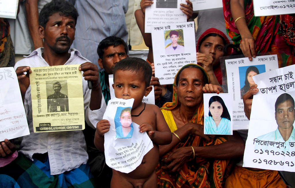 . Bangladeshi people hold photographs of their relatives whom they believe are trapped in the rubbles of a building that collapsed in Savar, outskirts of Dhaka, Bangladesh, Tuesday, April 30, 2013.  (AP Photo/Palash Khan)