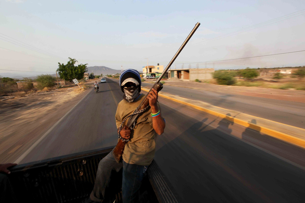. In this May 20, 2013 photo, an armed man belonging to a local self-defense group patrols from the back of a pick-up truck in the town of Buenavista, Mexico. Self-defense groups started to spring up in February to fight back the Knights Templar drug cartel which is extorting protection payments from cattlemen and lime growers, butchers and even marijuana growers. The federal government sees both the self-defense forces and the cartel as dangerous enemies. (AP Photo/Marco Ugarte)