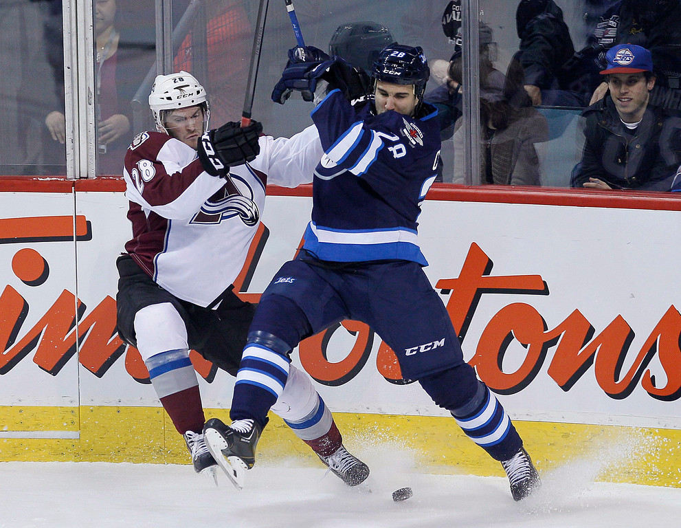 . Colorado Avalanche\'s Paul Carey (28) and Winnipeg Jets\' Patrice Cormier (28) fight for the puck during the first period of an NHL hockey game Wednesday, March 19, 2014, in Winnipeg, Manitoba. (AP Photo/The Canadian Press, John Woods)