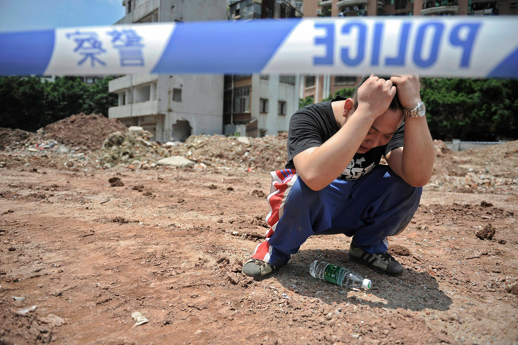 . Xian Xiyong, son of Li Jie\'e, cries next to a police line after his mother jumped off a building and died at a demolition site of Yangji village in Guangzhou, Guangdong province May 10, 2012. Li Jie\'e, a resident of Yangji village, jumped off a building and died on Thursday after her house was demolished on March 21, local media reported. REUTERS/Stringer