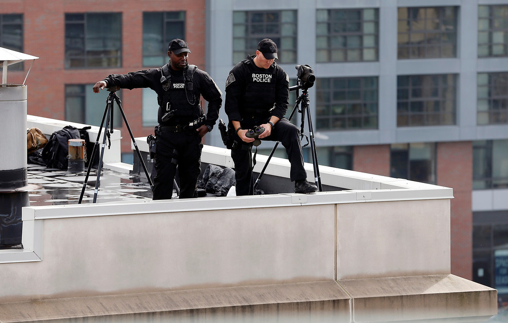. Boston police stand watch on a building adjacent to Fenway Park before Game 1 of baseball\'s American League division series between the Boston Red Sox and the Tampa Bay Rays, Friday, Oct. 4, 2013, in Boston. (AP Photo/Michael Dwyer)