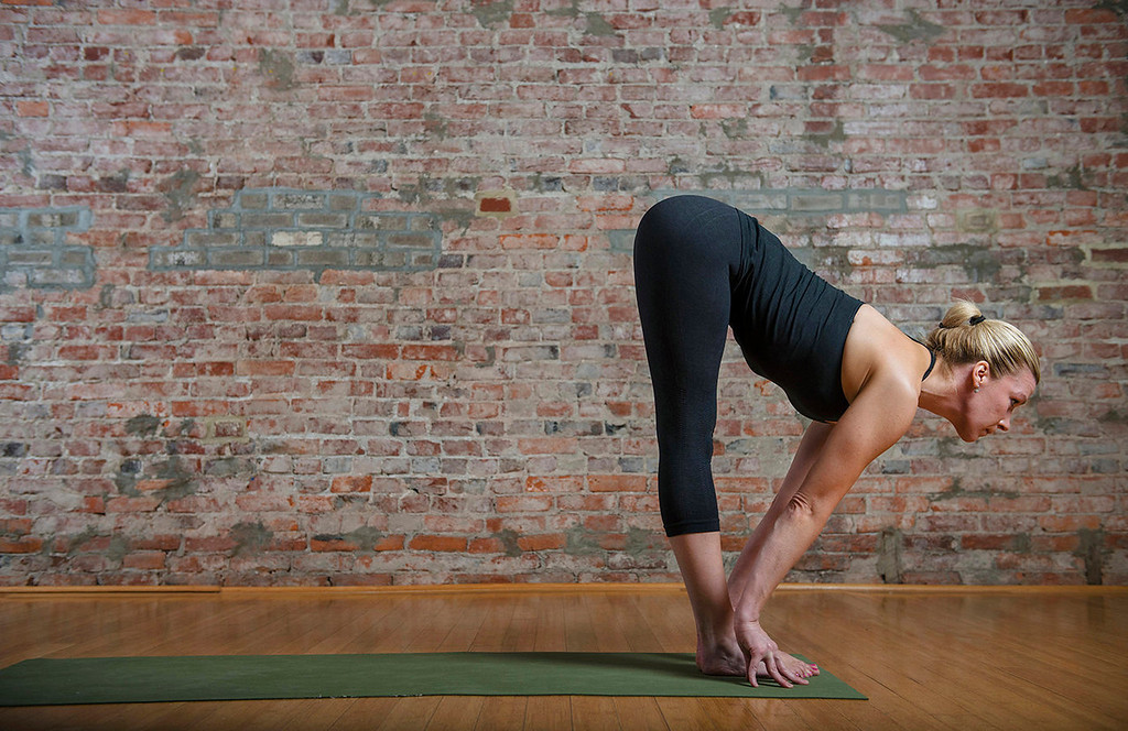. Sun salutation, left to right:  10) Return to the straight back forward fold with your spine extended and your gaze forward.  (Photo for The Washington Post by Amanda Voisard.)
