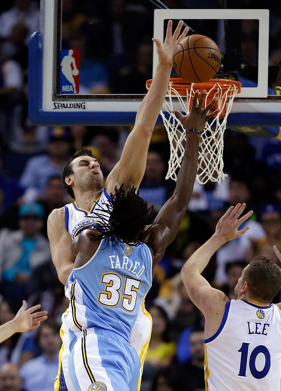 . Andrew Bogut #12 of the Golden State Warriors blocks a shot taken by Kenneth Faried #35 of the Denver Nuggets at ORACLE Arena on January 15, 2014 in Oakland, California. (Photo by Ezra Shaw/Getty Images)