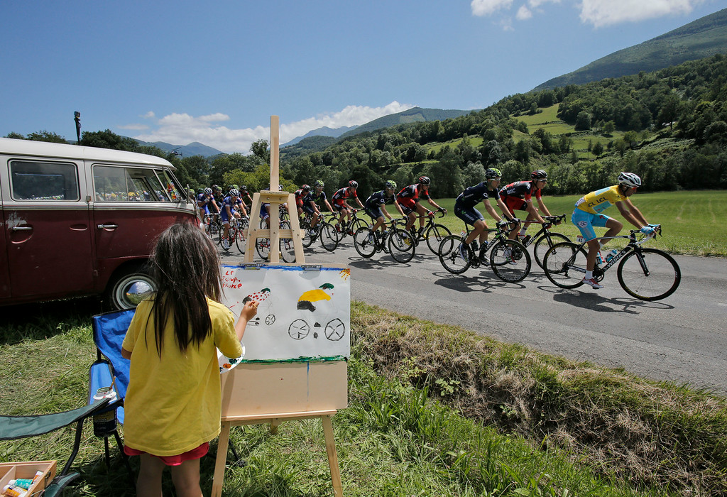 . A child makes a drawing as the pack with Italy\'s Vincenzo Nibali, wearing the overall leader\'s yellow jersey, passes during the sixteenth stage of the Tour de France cycling race over 237.5 kilometers (147.6 miles) with start in Carcassonne and finish in Bagneres-de-Luchon, France, Tuesday, July 22, 2014. (AP Photo/Christophe Ena)