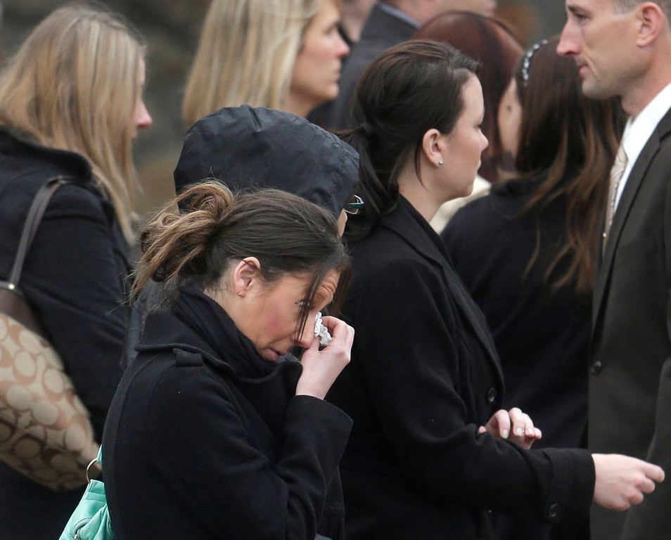 . A mourner reacts as she departs St. Patrick\'s Church in Stoneham, Mass., with others following a funeral Mass for Massachusetts Institute of Technology police officer Sean Collier, Tuesday, April 23, 2013. Collier was fatally shot on the MIT campus Thursday, April 18, 2013. Authorities allege that the Boston Marathon bombing suspects were responsible. (AP Photo/Steven Senne)