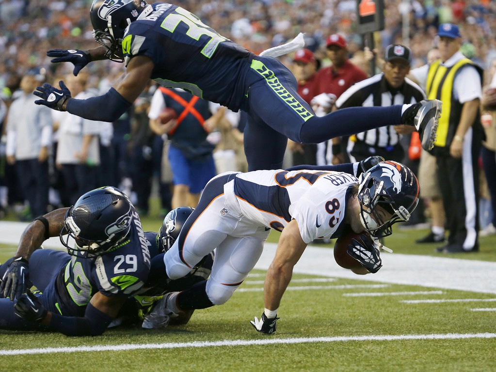 . Denver Broncos wide receiver Wes Welker scores a touchdown under the defense of a leaping Seattle Seahawks cornerback Brandon Browner (39) and tackles by Seahawks\' Earl Thomas (29) and Antoine Winfield (obscured) in the first half of a preseason NFL football game, Saturday, Aug. 17, 2013, in Seattle. (AP Photo/Elaine Thompson)