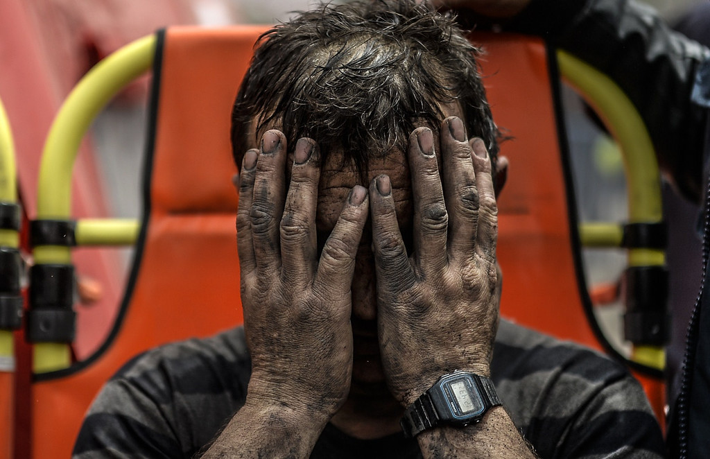 . A miner reacts after being affected with toxic gas while searching for co-workers who remain trapped underground on May 14, 2014 after an explosion and fire in their coal mine in the western Turkish province of Manisa killed at least 201 people. AFP PHOTO/BULENT  KILIC/AFP/Getty Images