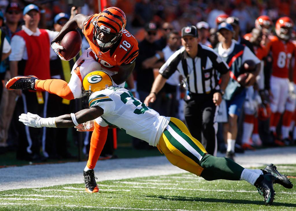 . Cincinnati Bengals wide receiver A.J. Green (18) is tackled by Green Bay Packers cornerback Sam Shields in the second half of an NFL football game, Sunday, Sept. 22, 2013, in Cincinnati. Cincinnati won 34-30. (AP Photo/David Kohl)