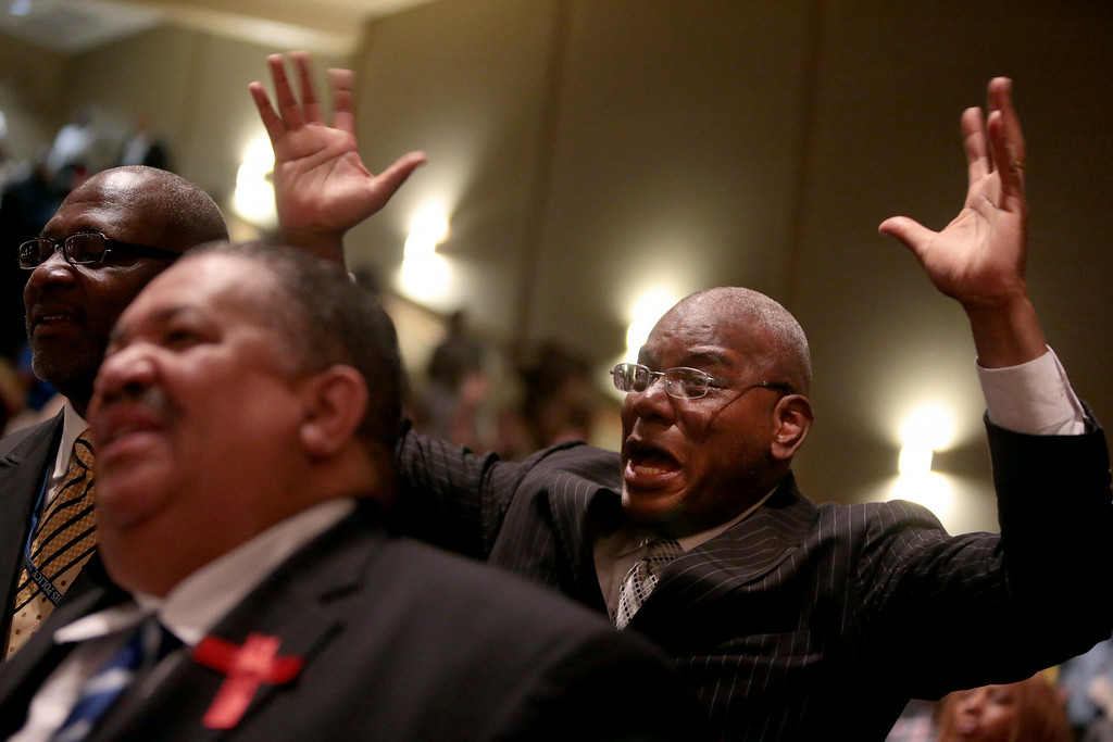 . A man reacts to a sermon during the funeral services for Michael Brown on Monday, Aug. 25, 2014, at Friendly Temple Missionary Baptist Church in St. Louis. Hundreds gathered to say goodbye to Michael Brown, the 18-year-old shot and killed Aug. 9 in a confrontation with a police officer that fueled almost two weeks of street protests. (AP Photo/St. Louis Post Dispatch, Robert Cohen, Pool)