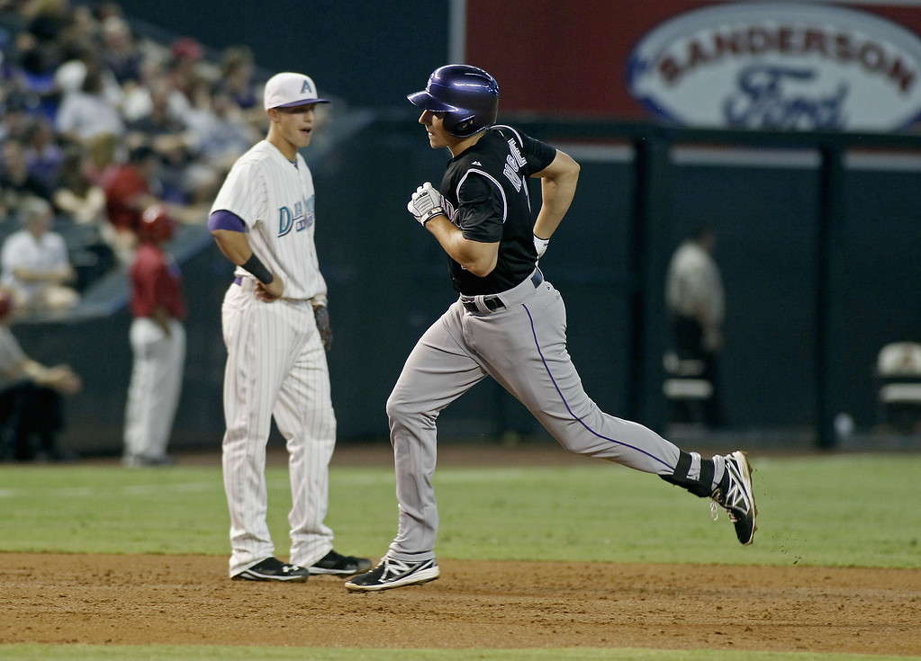 . Matt McBride #7 of the Colorado Rockies (R) runs past third baseman Jake Lamb #19 of the Arizona Diamondbacks following his solo home run during the second inning of a MLB game at Chase Field on August 30, 2014 in Phoenix, Arizona. (Photo by Ralph Freso/Getty Images)