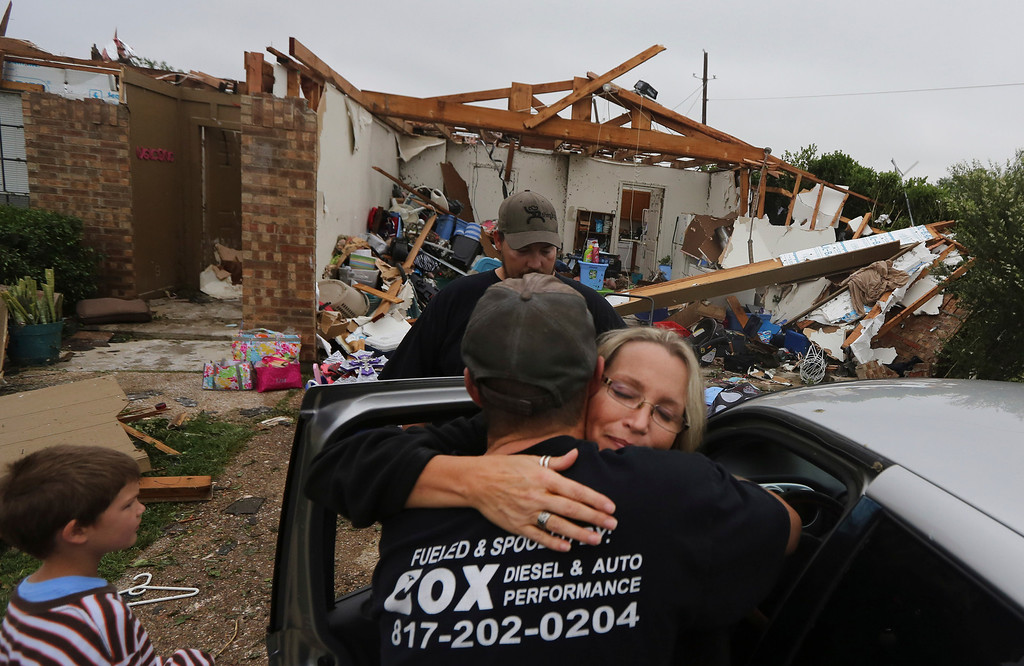 . Lisa Montgomery, right, hugs her nephew Jeremy Hulce as her sons Dillon Montgomery, 10, left, and Derrek Girsham look on in front of her home that was destroyed by a tornado in Cleburne, Texas, Thursday, May 16, 2013.  Ms. Montgomery rode out the twister the night before in her bathtub with her 10-year-old son. (AP Photo/LM Otero)